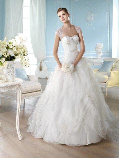 Изумительное свадебное платье линии Dreams известного испанского бренда St. Patrick Pronovias Fashion Group.  Удлинённый лиф обвит горизонтальной драпировкой.  Область бюста с линией декольте в форме «сердечка» расшита вертикальными строчками бисера и оригинальными цветочками.  Изюминка свадебного платья – широкие рукава «крылышки» - украшены таким же способом, формируют на спинке вырез «замочная скважина», а спереди – модифицированное декольте «королевы Анны».  На талии – пояс-лента с декоративной аппликацией и бантом. Волны полос тюльмарина моделируют верхний слой пышной юбки с небольшим шлейфом.