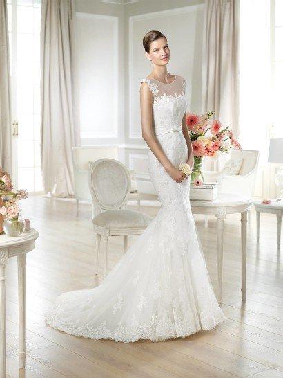 Элегантное узкое недорогоесвадебное платье с аккуратным шлейфом бренда White One Pronovias Fashion Group.  Прозрачная сетка, прикрывающая область декольте, очерчена вырезом «лодочка».  Рукава «крылышки» образуют на спинке глубокий V-образный вырез, продолжающийся длинным клином шнуровки.  Красивый кружевной декор, покрывающий платье до уровня колен, слетает отдельными фрагментами к подолу с купонной каймой.  На талии – оригинальный пояс с бантиком по центру переда.