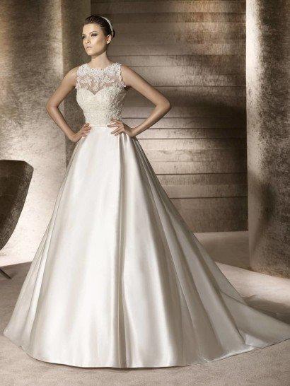 Изысканный блеск атласной ткани делает пышное свадебное платье особенно красивым и притягательным.  Открытый лиф с традиционным декольте в форме сердечка покрыт полупрозрачной тканью, по которой располагаются выразительные кружевные аппликации с фактурным рисунком.  Талию соблазнительно обрисовывает широкий пояс с кружевным декором.  Завершает образ потрясающей красоты шлейф.