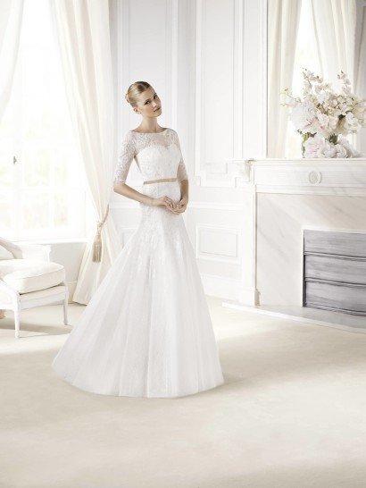 Свадебное платье прямого силуэта изысканно дополняет тонкий золотистый пояс на талии.  Небольшой шлейф придает образу особенную элегантность, которая подчеркивается и вырезом-лодочкой, и мелким рисунком тонкого кружева.  Кружевной верх декорирует декольте «сердечком» и выделяет форму плеч и рук.  Сзади, на спинке свадебного платья, расположен ряд декоративных пуговиц.  Нежная отделка на лифе и корсаже гармонично сочетается с матовой тканью юбки без аппликаций.