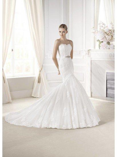 Открытое свадебное платье силуэта «русалка» позволяет создать очень женственный образ невесты.  Облегающий крой верха с декольте сердечком подчеркивает всю красоту фигуры, а небольшой ширины пояс на спине завязывается кокетливым бантом.  Подчеркивает настроение и отделка из кружев, покрывающая все свадебное платье.  Многослойная юбка со средней длины шлейфом и ажурным нижним краем выполнена из матового атласа и фатина.  Длинный пояс с завязанным сзади бантом гармонично повторяет ее форму.