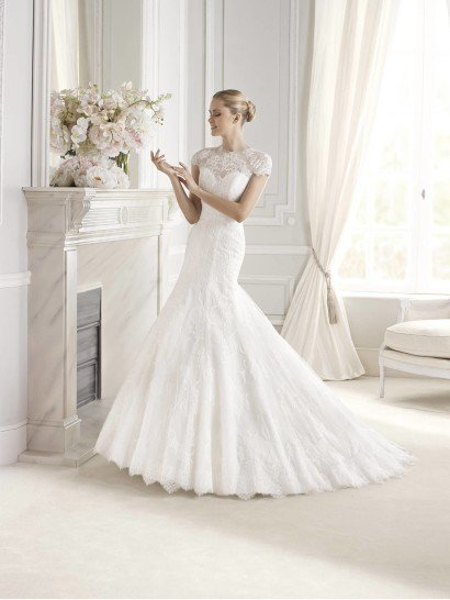 Элегантное свадебное платье с заниженной талией и юбкой А-силуэта создает особое романтичное настроение.  Закрытый верх из полупрозрачной ткани поддерживает впечатление сдержанной женственности.  А крупный цветочный рисунок кружева и декольте в форме «сердечка» выглядят достаточно соблазнительно и кокетливо.  Пышная юбка из нескольких слоев матовой ткани отделана кружевной аппликацией, нижний край задекорирован широкой полосой кружев.  Небольшой шлейф дополняет торжественность образа.