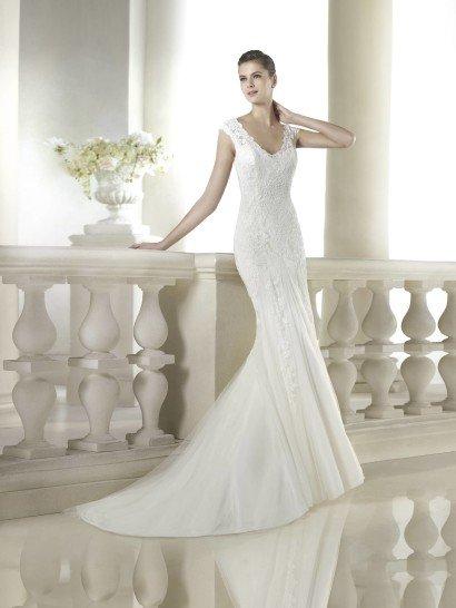 Свадебное платье с силуэтом русалка и шлейфом средней длины подчеркивает всю красоту женской фигуры, оставаясь при этом достаточно сдержанным.  Кружевной верх с широким V-образным вырезом и широкими бретелями идеально подходит для того, чтобы продемонстрировать форму рук и соблазнительное декольте.  Отделка выполнена из кружева. Особенно привлекательно смотрится спинка свадебного платья, оформленная полупрозрачной узорчатой тканью с рядом декоративных пуговиц.