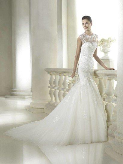 Свадебное платье силуэта «русалка» идеально подчеркивает изгибы фигуры невесты.  Пышная юбка выполнена из воздушного матового фатина, благодаря чему роскошный шлейф платья не кажется тяжеловесным и не стесняет движений.  Декольте платья в форме «сердечка» закрыто полупрозрачной тканью с кружевной отделкой.  Нежные кружева с мелким цветочным мотивом украшают также лиф и корсаж свадебного платья, небольшие аппликации расположены и на юбке.