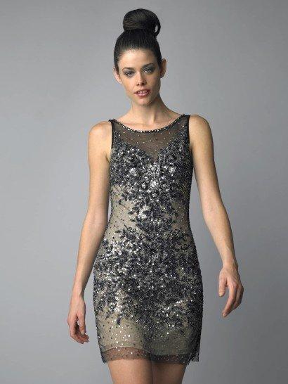 Коктейльное платье с американской проймой смотрится необычно благодаря многослойности ткани.  В качестве основы использован пудрово-бежевый чехол с открытым декольте, а верхний слой выполнен из черной полупрозрачной ткани, с бретелями и чуть более длинной юбкой.  Вечернее платье декорировано сияющими камнями, бисером и пайетками.  Узор, концентрирующийся в области декольте и на линии бедер, делает фигуру визуально стройнее.