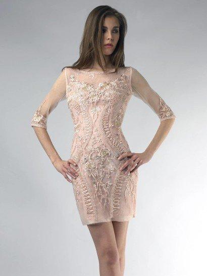 Коктейльное платье светлого розового оттенка смотрится нежно и романтично.  Полупрозрачный рукав средней длины и вырез бато подчеркивают изящество силуэта, а короткая юбка открывает ноги.  Вечернее платье полностью расшито тесьмой в тон и украшено небольшими стразами.  Красивый цветочный узор, который образует отделка, гармонично сочетается с цветом ткани, создавая особенное настроение.