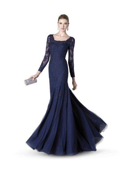 Элегантное вечернее платье насыщенного чернильно-синего оттенка привлекает внимание длиной в пол и красивой отделкой из полупрозрачного материала.  Длинный ажурный рукав выделяет форму рук, а кружевной вырез подчеркивает область декольте.  От лифа до середины бедра вечернее платье расшито сверкающим бисером, а низ юбки украшает верхний слой из легкой прозрачной ткани в нежный темно-синий горошек.  Вечернее платье из коллекции It's My Party/ Pronovias Fashion Group /  Платье идеальноподойдет для встречи Нового года 2018!