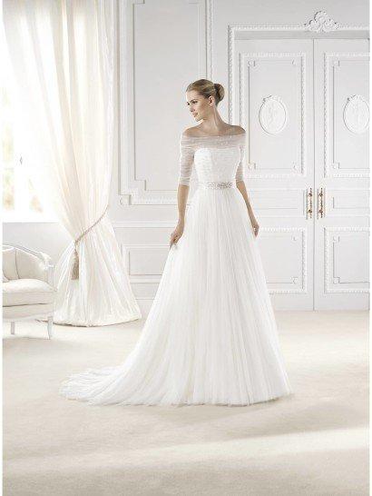 Элегантное свадебное платье очаровывает трогательной линией декольте с заниженными рукавами из полупрозрачной ткани, которые достигают локтя.  Хрупкий силуэт, созданный сочетанием такой отделки и кроя с объемной юбкой, подчеркнут поясом на талии.  Длинную юбку украшают многочисленные тонкие драпировки воздушной ткани, сзади ниспадающие в небольшой, но очень красивый шлейф.