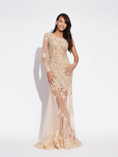 Необычное вечернее платье из полупрозрачной ткани с золотистой отделкой создаст неотразимый и соблазнительный образ.  Ассиметричный рукав и участки прозрачного материала подчеркивают красоту женственной фигуры, а длинный подол придает ей особую элегантность.  Плотная золотая отделка скрывает область лифа и бедер, а также покрывает рукав и нижний край юбки абстрактным рисунком.
