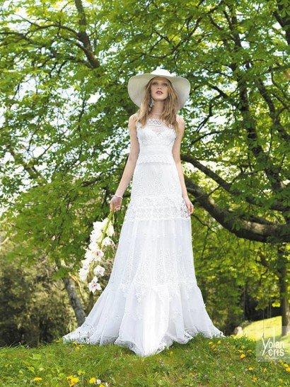 Стильное свадебное платье в стиле бохо отличается элегантным и непринужденным прямым кроем и выразительной текстурой ткани. Лиф с тонкими бретелями полностью покрыт кружевом с абстрактным рисунком.  Прямая юбка выполнена из нескольких слоев ткани, верхний из которых полупрозрачный, и декорирована кружевом и вышивкой, расположенных горизонтальными уровнями по всей длине свадебного платья.  Свадебные платья Yolan Crisэксклюзивно представлены в салоне Виктория  Примерка платьев Yolan Cris -платная