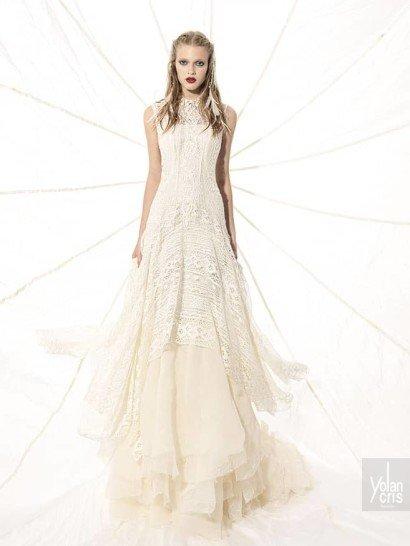 Закрытое свадебное платье в утонченном богемном стиле облегает фигуру прямым кроем лифа сверху, ниже переходя в пышную многослойную юбку из фактурной сетчатой ткани.  Закрытый верх выполнен из полупрозрачного материала, скрывающего более плотную основу с прямой линией выреза.  Верхний слой ткани на юбке – ажурный, с геометрическим рисунком. Он спускается крупными волнами, придавая сетчатой ткани особенный объем.  Свадебные платья Yolan Crisэксклюзивно представлены в салоне Виктория  Примерка платьев Yolan Cris -платная