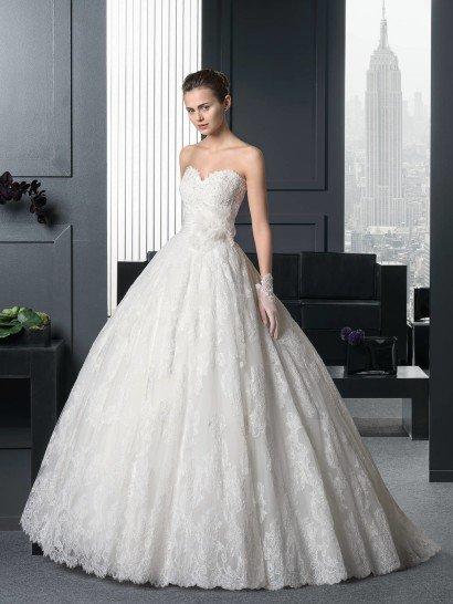 Романтичное свадебное платье пышного силуэта по всей длине декорировано нежным кружевом.  На открытом лифе в форме сердца оно образует фигурный край, как и на нижней части подола многослойной юбки из тюльмарина.  Сзади юбку украшает торжественный шлейф.  Оригинальным дополнением образа служит широкий пояс, декорированный горизонтальными драпировками тонкой ткани и объемным цветком с полупрозрачными лепестками, расположенным сбоку.