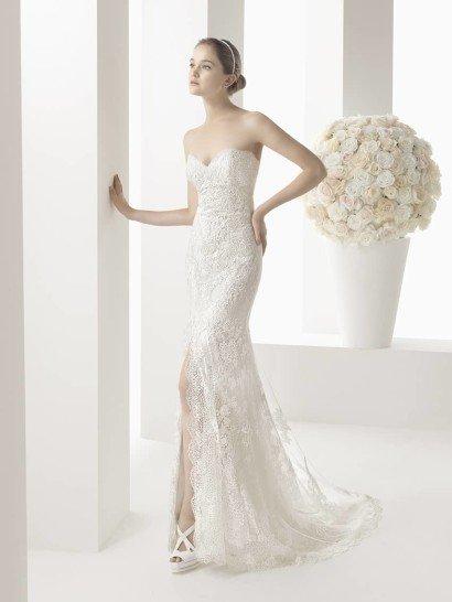 Прямое свадебное платье соблазнительно облегает фигуру, открывая ноги роскошным разрезом до середины бедра.  Тонкий слой кружева с цветочным рисунком покрывает его по всей длине, придавая образу утонченную женственность, подчеркнутую элегантным лифом в форме сердечка.  По краям разреза кружевная ткань украшает юбку фигурными выступами, которые продолжаются и по шлейфу средней длины, ниспадающему сзади.