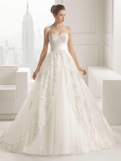 Открытое свадебное платьеSALVA выразительно акцентирует талию широким поясом с фактурными горизонтальными драпировками.  Лиф в форме сердечка покрыт плотным слоем кружева, которое делает край декольте фигурным, а юбку украшает полупрозрачный верхний слой ткани, который спереди открывает нижние слои тюльмарина высоким разрезом, по краям оформленным кружевными аппликациями.