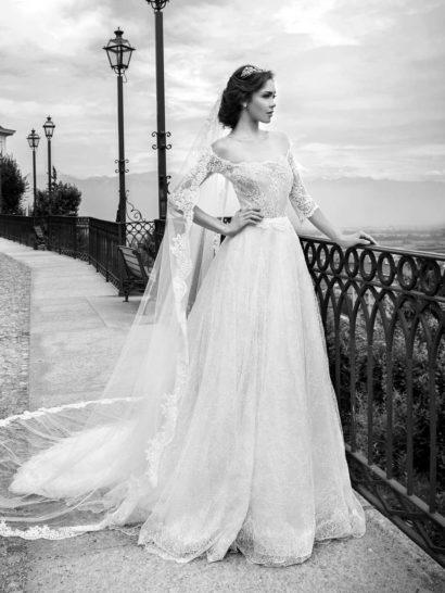 Роскошное свадебное платье акцентирует хрупкую линию плеч и изящество шеи невесты округлым портретным декольте.  Верх с рукавами длиной до локтя выполнен из ткани, создающей иллюзию прозрачности.  Многослойная юбка создана на плотной белой основе, покрытой легким слоем фактурного кружева с плотным мелким рисунком.  Нижняя часть подола покрыта широкой полосой ажурных фестонов, которые продолжаются и по пышному шлейфу сзади.