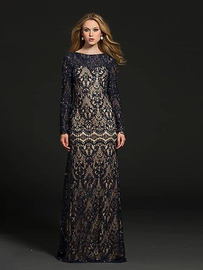 Элегантное вечернее платье прямого кроя спускается до самого пола, а закрытый верх с вырезом под горло скрывает руки длинными облегающими рукавами.  Бежевая ткань подкладки использована на юбке и лифе, где образует корсет с декольте сердечком.  Поверх располагается плотное синее кружево с абстрактным узором, дополненное сияющей вышивкой из бисера, подобранного в тон ткани.