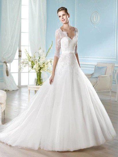 Пышное свадебное платье с элегантным шлейфом сзади идеально подходит для создания торжественного настроения.  Женственный лиф в форме сердечка дополняет тонкое кружево с мелким узором, покрывающее корсет, обрамляющее область декольте и создающее прямые рукава длиной до локтя, заканчивающиеся фигурными манжетами.  Талию выделяет узкий атласный пояс с небольшим бантом спереди.