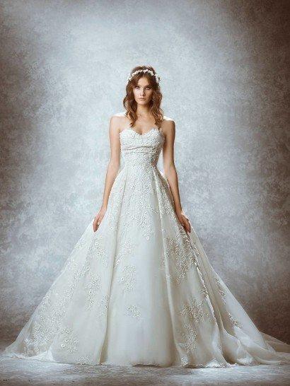 Открытое свадебное платье облегает фигуру роскошной фактурной тканью, на корсете покрытой плотным кружевным узором, который подчеркивает романтичное настроение лифа в форме сердца, а на юбке – лишь декорированной акцентами объемного цветочного рисунка, делающего многослойность низа выразительнее и торжественнее.  Юбку завершает потрясающий пышный шлейф, расходящийся широким веером.  Платье изготовлено вручную.    В НАЛИЧИИ