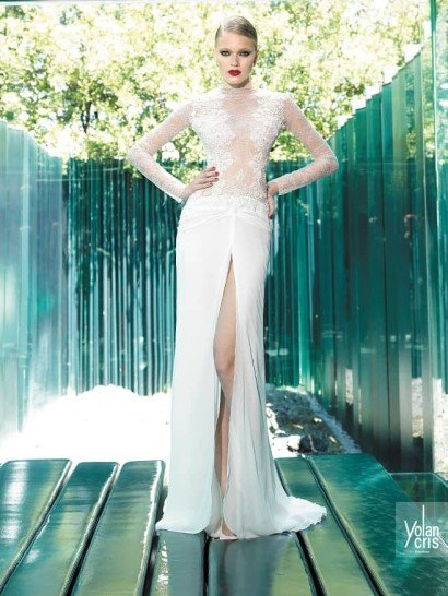 Прямое свадебное платье создает чувственный образ, сверху подчеркнутый тканью, создающей иллюзию прозрачности, а снизу, на лаконичной юбке – высоким разрезом до середины бедра, расположившемся сбоку подола.  Закрытый верх с вырезом под горло и длинными облегающими рукавами декорирован широкими вертикальными полосами кружева с плотным цветочным узором, которое также образует горизонтальную полосу по талии.  Свадебные платьяYolanCrisэксклюзивно представлены в салоне Виктория  Примерка платьевYolan Cris—платная