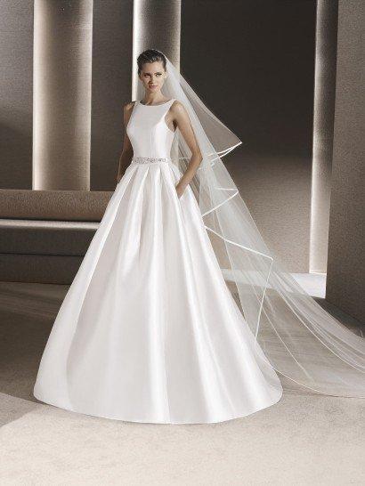 """Закрытое свадебное платье идеально для создания самого утонченного и женственного образа.  Элегантный верх с вырезом """"лодочкой"""" красиво обрисовывает фигуру, подчеркивая форму шеи.  Лаконично украсить верх помогают вертикальные швы.  Талия подчеркивается узким атласным поясом, спереди декорированным вышивкой.  Пышная юбка спускается объемными вертикальными складками, а по бокам ее дополняют скрытые карманы."""