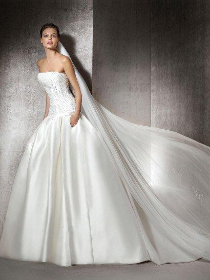 Неподражаемый образ создаст роскошное свадебное платье из глянцевого атласа.  Объемная юбка, декорированная крупными вертикальными складками ткани, спускающимися полосами по всему подолу, переходит сзади в потрясающий полукруг шлейфа.  Лаконичный открытый корсет с лифом прямого кроя и декоративными швами изысканно украшен слоем вышивки из крупных белых бусин - они будто бы создают на ткани узор в горошек.