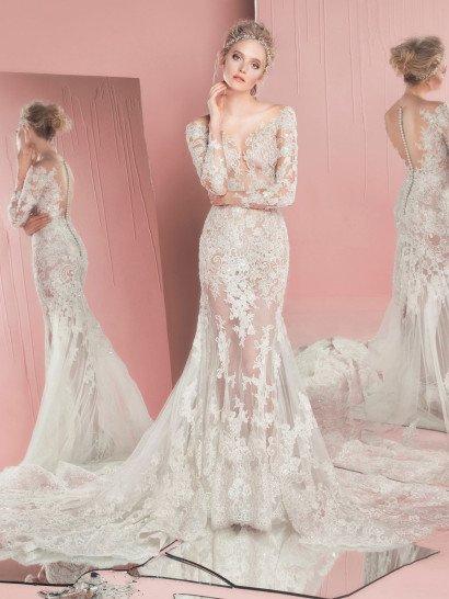 Нежность и изящество силуэта невесты идеально подчеркиваются облегающим свадебным платьем силуэта «русалка», воплощенным в тонкой ткани.  Ее по всей длине декорируют аппликации из белого кружева, образующие V-образный вырез на лифе и глубокое фигурное декольте на спинке, также украшенной вертикальным рядом декоративных пуговиц.  Юбку украшает роскошный пышный шлейф, расшитый кружевом и бисером.  Платье изготовлено вручную.    В НАЛИЧИИ