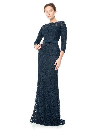 Темно-синее вечернее платье создано для ценительниц лаконичных и женственных образов.  Его элегантный прямой крой с рукавами длиной в три четверти и вырезом под горло обрисовывает фигуру стильно и сдержанно.  Украшением образа служит фактурное кружево в тон ткани, покрывающее вечернее платье по всей длине.  В качестве аксессуара используется деликатный пояс, декорированный лишь небольшим бантом по середине.  Есть платья больших размеров.