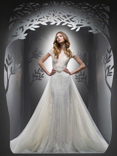 Великолепное свадебное платье с роскошной верхней юбкой силуэта «принцесса» элегантно обрисовывает силуэт нижней юбкой облегающего кроя.  И подкладку, и верх декорируют изящные кружевные аппликации.  Закрытый лиф позволяет привнести в образ утонченную скромность.  Его округлый вырез под горло дополнен короткими рукавами прямого кроя.  Ткань верха полностью декорирована кружевом, а талию украшает фактурный пояс.
