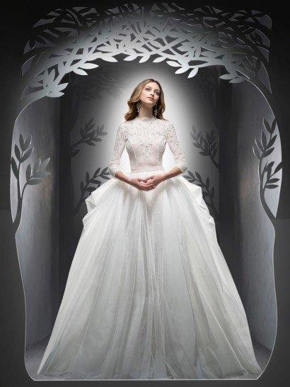 Свадебное платье-трансформер. Впечатляющая пышная юбка закрытого свадебного платья украшена по бокам объемными складками полупрозрачной ткани, делающими образ особенно торжественным и драматичным.  Контрастно с многослойностью низа выступает тонкий облегающий верх с кружевным декором.  Его высокий фигурный воротник и длинные рукава смотрятся сдержанно и стильно, а подчеркнуть в силуэте талию помогает узкий пояс без отделки.