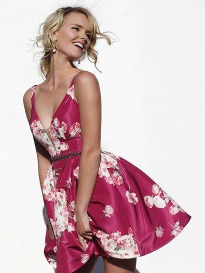 Короткое вечернее платье притягивает взгляды необычным крупным принтом в виде бело-розовых бутонов, стильно дополняющим насыщенный малиновый оттенок атласной ткани.  Юбка длиной до середины бедра смотрится торжественно благодаря выразительному объему, а верх соблазнительно подчеркивает фигуру глубоким V-образным вырезом декольте.  Естественную линию талии позволяет подчеркнуть фигурный пояс с блестящей вышивкой бисером.