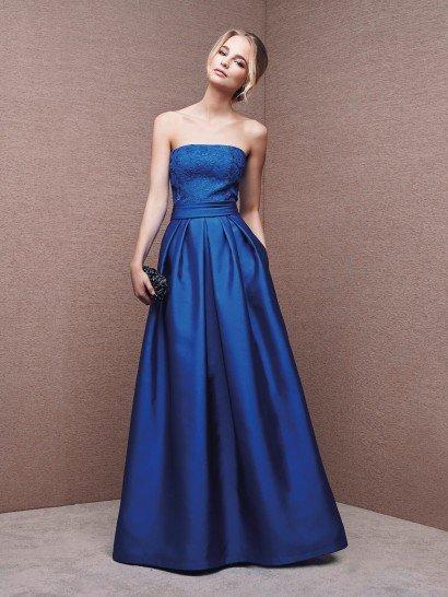 Невероятно изысканным стилем отличается атласное вечернее платье глубокого синего цвета, лаконично облегающее область декольте прямым лифом и эксцентричными скрытыми карманами по бокам сдержанного подола, украшенного лишь фактурными складками ткани.  Главный акцент в силуэте сделан на талию – с помощью широкого пояса из атласа.  Верх вечернего платья декорирует тонкий слой кружева, подобранного в цвет атласной ткани.