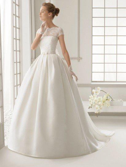 Пышное свадебное платье с элегантным шлейфом сзади.  Платье имеет лаконичную фактуру плотного шелка и нежное кружево, покрывающее корсет.  Кружевная ткань продолжается над открытым лифом прямого кроя, создавая фигурный вырез лодочкой и короткие облегающие рукава.  На талии располагается узкий пояс с небольшим бантом спереди, на спинке он украшен пышным цветком, который располагается под глубоким V-образным вырезом декольте с ажурным краем.