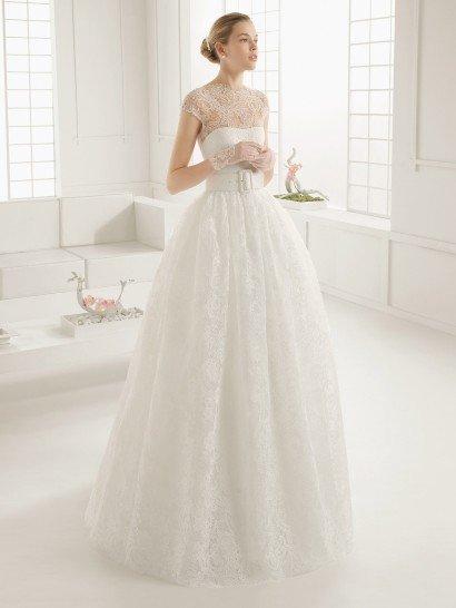 Пышное свадебное платье оригинально дополняет широкий пояс с прямоугольной пряжкой по середине.  Открытый лиф с легким изгибом декольте покрыт кружевной тканью с мелким рисунком – она образует короткие рукава и женственный фигурный вырез под горло, а также полностью закрывает глубокое декольте, созданное на спинке корсетом.  Такая же нежная кружевная ткань покрывает и юбку, спускаясь от талии объемными складками.