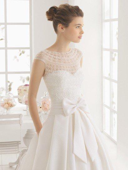 Пышное свадебное платье выполнено из пикейной ткани с кружевным верхом.