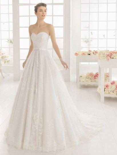 Элегантное свадебное платье с открытым корсетом выполнено из тюля и кружева, сочетающихся романтичным дуэтом.  На талии располагается узкий атласный пояс с бантом спереди.  Юбка покрыта вертикальными складками ткани, сзади переходящими в шлейф, край которого оформлен фигурной полосой кружева, красиво дополняющей крупные кружевные аппликации по всей длине подола.