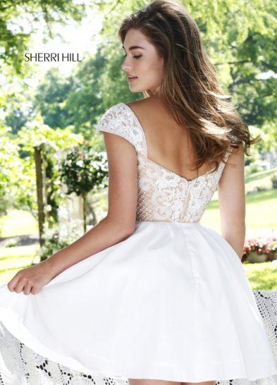 Короткое выпускное платье белого цвета с выразительной отделкой верха.