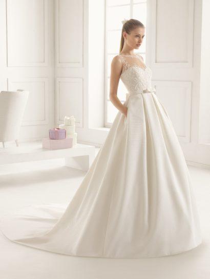 Мягкий глянцевый блеск роскошного шелка, из которого выполнено пышное свадебное платье, дополнен по корсету тонкой вставкой, скрывающей лиф в форме сердца и декорирующей спинку.  По ткани отделки проходит крупный кружевной узор, покрывающий корсет, обрисовывающий округлый вырез и линии декольте сзади.  В качестве акцента в образе выступает узкий пояс, на спинке украшенный объемным бутоном. Юбку декорируют скрытые карманы.