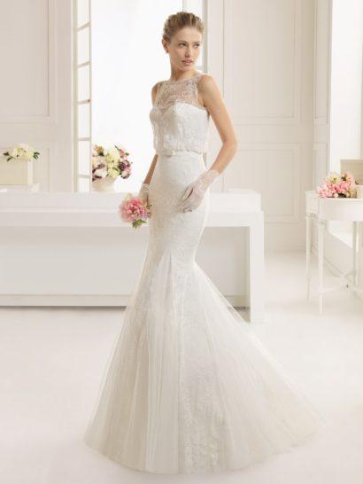 Элегантное свадебное платье с силуэтом «русалка» обрисовывает декольте лифом в форме сердечка, но при этом смотрится сдержанно благодаря тонкой ажурной ткани, располагающейся верхним слоем по всей длине.  На талии располагается узкий пояс, украшенный спереди бантом.  Юбку декорируют вертикальные складки ткани, спускающиеся от коленей вниз полупрозрачными волнами, а сзади она дополнена небольшим шлейфом.