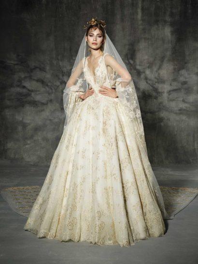 Невероятно роскошное свадебное платье с подчеркнуто пышным силуэтом выполнено из белой ткани с декором из золотистого кружева.  Верх с V-образным декольте с фигурным краем, созданным узкими симметричными бретелями, позволяет выразительно подчеркнуть фигуру.  Потрясающая юбка из нескольких слоев ткани по всей длине украшена сияющим кружевным узором, который становится плотнее к нижнему краю подола.  Сзади юбку также декорирует шлейф, дополнить образ можно фатой.  Свадебные платья Yolan Crisэксклюзивно представлены в салоне Виктория  Примерка платьев Yolan Cris —платная