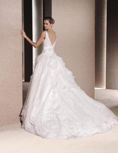 Свадебное платье пышного силуэта из глянцевой ткани с длинным шлейфом.