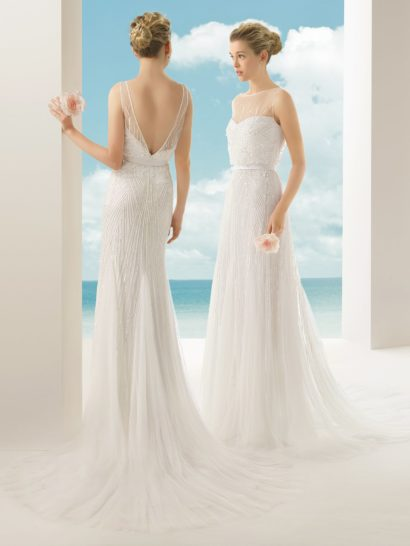 Утонченность образа свадебного платья с прямым силуэтом впечатляет в первую же секунду.  Спинку обнажает глубокий V-образный вырез, обрамленный полупрозрачной тканью, а верх, напротив, закрыт вставкой до самой шеи.  Нежный геометрический узор из сияющего бисера покрывает ткань платья по всей длине, меняя очертания силуэта.  Выделить талию помогает узкий пояс из глянцевого атласа, а юбка сзади завершает образ легким шлейфом.