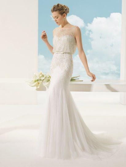 Деликатный открытый лиф свадебного платья дополнен тонкой тканью, создающей над корсетом изящную блузу с округлым вырезом и отделкой из сверкающей бисерной вышивки.  На талии – узкий атласный пояс, украшенный спереди бантом.  Юбку с полупрозрачным шлейфом сзади по верхней части подола декорирует такая же вышивка из бисера, как и на лифе платья.