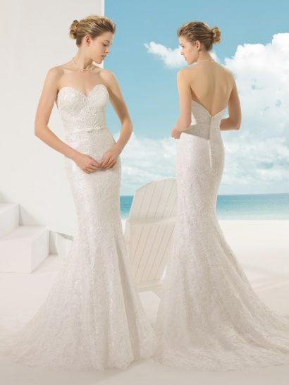 Свадебное платье, обрисовывающее изгибы силуэта кроем «русалка», покрыто слоем тонкого кружева с легким глянцевым блеском.  Изящную ткань поддерживает такое же настроение декора – спинку платья украшает вертикальный ряд пуговиц, а спереди акцент сделан лишь на линию талии, выделенную узким поясом с маленьким бантом.  Главным украшением юбки становится шлейф из нескольких слоев ткани.