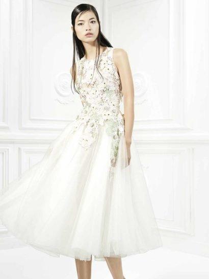 Короткое белое вечернее платье с юбкой до колена ( чайной длины ) позволяет создать образ наполненный элегантностью и индивидуальным стилем.   Верх на бежевой подкладке, обрисовывающий шею округлым вырезом, создает иллюзию прозрачности. Он полностью покрыт белым кружевом с крупным цветочным рисунком, дополненным зелеными акцентами. Подол укрыт несколькими слоями полупрозрачной белой ткани.