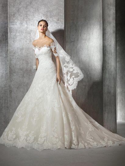 Утонченное свадебное платье с роскошной юбкой силуэта «принцесса», созданной из нескольких слоев ткани с верхом, декорированным небольшими кружевными аппликациями.  Классический лиф в форме сердца декорирован кружевом, по бокам его дополняют короткие рукава прямого кроя, также украшенные аппликациями.  На спинке – глубокое фигурное декольте, укрытое прозрачной вставкой с вертикальным рядом декоративных пуговиц.