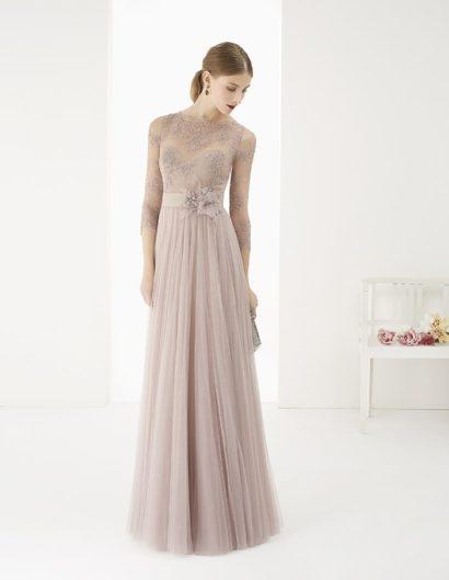 Прямое вечернее платье, выполненное в романтичном оттенке пепельной розы, идеально подойдет для обладательницы изысканного вкуса.  Лаконичный крой изящно дополняет тонкое кружево, закрывающее лиф и создающее облегающие рукава длиной в три четверти. Юбка покрыта узкими полосами вертикальных складок, а на талии располагается широкий пояс, украшенный сбоку объемным бутоном с легкими лепестками.
