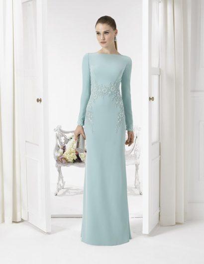 Создать изысканный и утонченный образ поможет стильное вечернее платье светло-голубого цвета, очерчивающее силуэт прямым кроем.  Закрытый верх оформлен элегантным вырезом «лодочка», который дополняют длинные рукава прямого кроя, выполненные из плотной ткани.  Деликатно дополнить образ помогает отделка, фигурной полосой очерчивающая естественную линию талии и спускающаяся по бокам вниз до бедер.