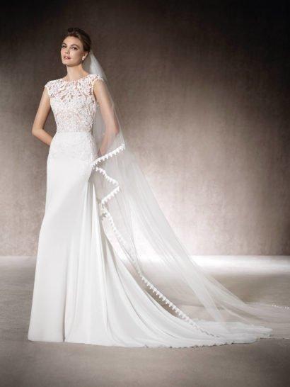 Элегантное свадебное платье прямого кроя удачно объединяет в одном образе лаконичную юбку без фактурной отделки, дополненную лишь длинным шлейфом, и романтичный полупрозрачный кружевной верх, выразительность которого помогает подчеркнуть деликатная подкладка в тон кожи.  Дополнить верх с округлым вырезом может помочь узкий пояс в бронзовом цвете.  Драматичной деталью служит открытая спинка сзади – вырез спускается почти до самой линии талии.