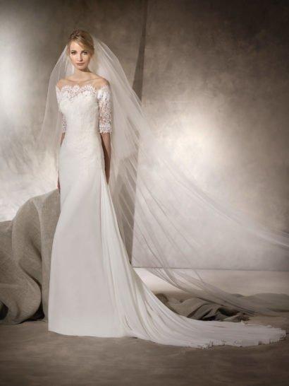 Прекрасное свадебное платье прямого кроя дополнено великолепным длинным шлейфом, спускающимся прямо от уровня бедер выразительными волнами ткани.  Притягивает взгляды эффектное кружевное декольте, открывающее плечи.  Плотное кружево украшает верх, из него созданы и прямые рукава длиной до локтя.  Кружевную спинку платья деликатно дополняет вертикальный ряд белоснежных пуговиц.