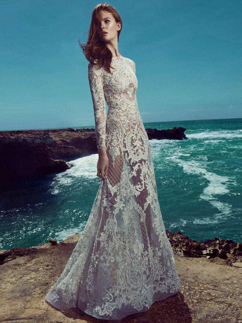 Закрытое свадебное платье с длинным рукавом, выполненное из кружевной ткани.